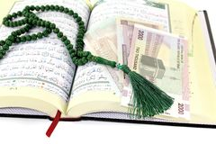 Whipped Quran with Iranian Rials. Before light background Stock Image