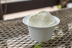 Whipping cream in the white cup on the metal table Stock Photography