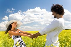 Whirling. Photo of attractive couple holding by hands and whirling on the meadow at leisure Royalty Free Stock Photos