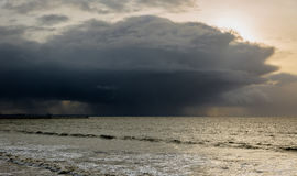 Whirling, black, solid storm clouds cover sun over a sea in Swan. Sea, Walls. Sun rays reflection in watter. Horizontal shot stock photography