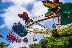 Whirling carousel with kids on the background of blue sky at the children& x27;s amusement park. Childrens fun in the  merry-go-round at the funfair against a Stock Images
