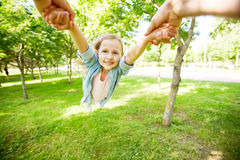 Whirling child. Hands of parent holding little girl and whirling her in park Stock Photo