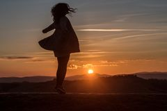 Whirling girl at sunset. Whirling girl in nature at sunset Stock Image