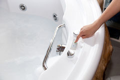 Whirlpool bath. White whirlpool bath with rock ready to take a bath stock image