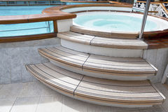 Whirlpool on the deck of a cruise ship. Whirlpool jacuzzi with wooden steps and pool on the deck of a cruise ship Royalty Free Stock Images
