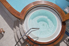 Whirlpool on the deck of a cruise ship. Whirlpool jacuzzi with wooden steps and pool on the deck of a cruise ship Stock Images