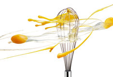 Whisk beating eggs. Isolated on white background Royalty Free Stock Photography