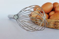 Whisk and eggs in rattan basket. Stock Image