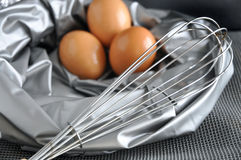 Whisk with eggs on silver color Stock Photo
