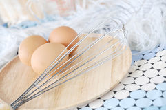 Whisk and eggs on wooden plate Royalty Free Stock Image
