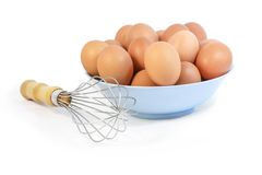 Whisk and Fresh Hen Egg in a bowl Royalty Free Stock Images