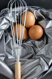Whisk in front of eggs on silver texture Royalty Free Stock Photos