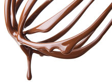 Whisk with melted chocolate over white Royalty Free Stock Photos