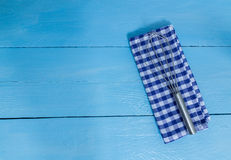 Whisk and tea towel on blue wooden background Royalty Free Stock Photos