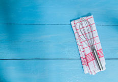 Whisk and tea towel on blue wooden background Stock Photography
