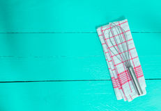 Whisk and tea towel on turquoise wooden background Stock Photo