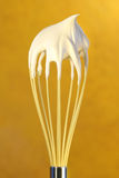 Whisk with whip cream on top Royalty Free Stock Photo