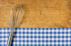 Whisk on wooden background with a blue checkered tablecloth. Whisk on a wooden background with a blue checkered tablecloth Stock Photos