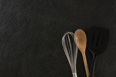 Whisker, wooden spoon and spatula. On black background stock images