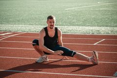A mustachioed runner stretches out Stock Photography