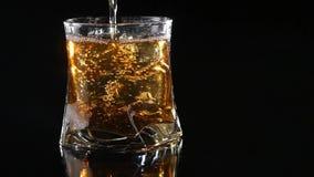 Whiskey étant versé dans un verre contre le noir
