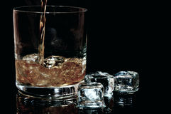Whiskey. Flows into a glass with ice cubes to the left against black background in the horizontal format Stock Image