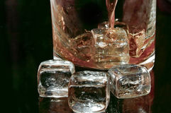 Whiskey. Flows into a glass with ice cubes to the right against black background in the horizontal format Stock Images