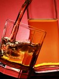 Whiskey. Pour into glass over red background royalty free stock image
