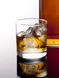 Whiskey. A glass of whiskey and bottle Royalty Free Stock Photography