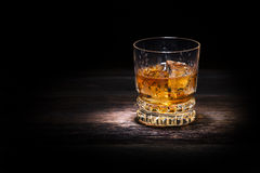 Whiskey. Glass of whiskey on wooden background close up royalty free stock image