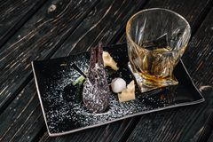 Whiskey and appetizer on black plate. On dark wood background Stock Photos