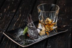 Whiskey and appetizer on black plate. On dark wood background Stock Photo