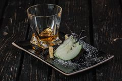 Whiskey and appetizer on black plate. On dark wood background Royalty Free Stock Images