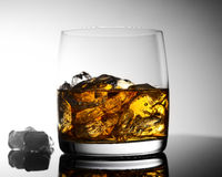 Whiskey avec de la glace dans un verre transparent sur une surface en verre Photos libres de droits