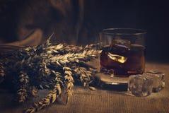 Whiskey on background with wheat straws toning photo Royalty Free Stock Photography