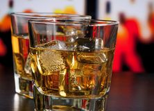 Whiskey on bar table with ice Stock Photo