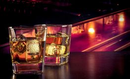 Whiskey on bar table with ice. Whiskey with ice on bar table lounge bar atmosphere Royalty Free Stock Photo