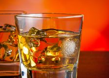 Whiskey on bar table with ice on warm atmosphere Stock Image