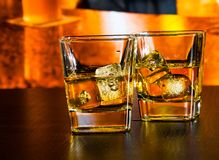 Whiskey on bar table with ice on warm atmosphere Royalty Free Stock Photos