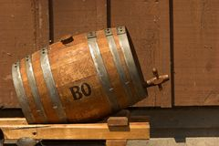 Whiskey barrel. Old oak whiskey barrel on the side of a wooden building royalty free stock photo