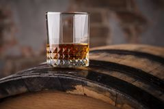 Whiskey on a barrel. Tumbler glass of whiskey standing on a barrel in a cellar stock images