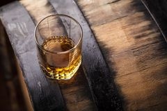 Whiskey on a barrel. Tumbler glass of whiskey standing on a barrel in a cellar royalty free stock photography