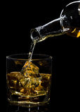 Whiskey being poured into a glass. Against black background Royalty Free Stock Photo