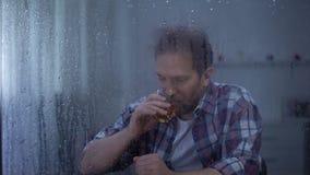 Whiskey bevente dell'uomo depresso da solo il giorno piovoso, pensante ai problemi di vita video d archivio