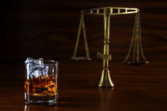Whiskey  and blurred scales of justice, concept alcohol and law Royalty Free Stock Image