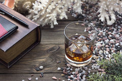 Whiskey and book. Whiskey and a book on the table with seashells Royalty Free Stock Images