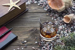 Whiskey and book. Whiskey and a book on the table with seashells Stock Image
