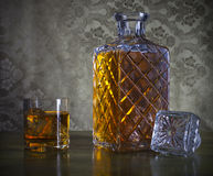 Whiskey in bottle and glass with ice Stock Images