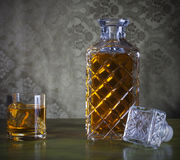 Whiskey in bottle and glass with ice Royalty Free Stock Photos