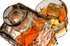 Whiskey Bottle & Glass Isolated. Ornate bottle and glass of whiskey and ice against white background Stock Photography